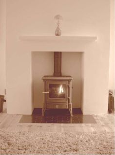 Rendered chamber with floating shelf, Victorian tiled hearth and wood stove. Fitted in Southchurch  Essex 2003
