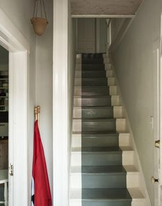 the bare stairs painted white with a runner-like band of charcoal gray. #stairs #painted_floor #runner_like_painted