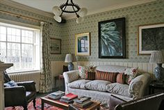 LUSH LIFE The walls of this sitting room are papered in Robert Kime's Voysey Trellis. Hanging above the Kime Priory sofa are a painting by Delli Lycett-Green (center) and a drawing by Lucian Freud (right).