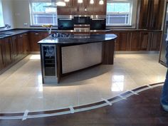 We love the transition between the polished porcelain tiles and wooden floor in this kitchen (Please excuse the tape! Tile To Wood Transition, Kitchen Tiles, Staining Cabinets, Tile Edge, Flooring, Patterned Floor Tiles, Tile Installation, Granite Flooring, Granite Floor Tiles