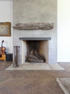 Truly eclectic - luxe, minimalist & rustic fireplace finished in concrete, reclaimed wood, with herringbone oak floors.