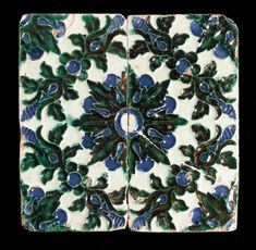 Two Spanish (Seville) lustred tiles first half 15th century Forming a single geometrical floral design edged by foliate borders and similar corner motifs, the moulded arista decoration picked out in blue and green heightened in copper lustre, all on a greenish white tin-glazed ground,