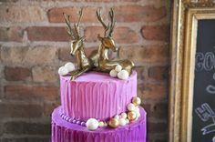 Gold-painted deer figurines and fondant balls adorn this Radiant Orchid-colored cake.