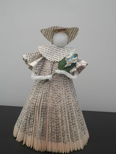 Lady made from a folded book with paper lily flowers.