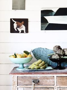 Lemons in an aqua ceramic bowl with interesting art - very vintage style - in the home of Sarah Murphy, Matthew McCaughey and Family as seen on The Design Files