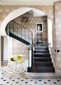 Vintage patterned wallpaper in entryway with yellow chair