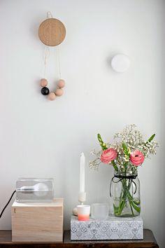 Ruokailutilan seinällä on Muuton The Dots -ripustimet. Tason päällä on kannellinen puulaatikko Granitista ja Harri Koskisen suunnittelema Block-valaisin. H&M Homen kuviollisen laatikon päällä on Bloomingvillen pieni purkki.