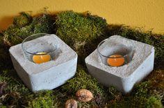 Quadratische Betonklotz mit eingelegten Kerzengläsli. Pickling