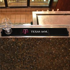Texas A&M Drink Mat 3.25x24 - Keep your freshly crafted drinks safe with our new officially licensed Drink Mats. Featuring your favorite team's logo. With a sleek design, our rubber Drink Mat offers an affordable, practical and high quality solution to protecting your bar top surfaces. Easy to clean, a rubber Drink Mat will collect spilt liquid and condensation, ideal when servicing pints and cocktails. FANMATS Series: DRINKMATTeam Series: Texas A&M UniversityProduct Dimensions…