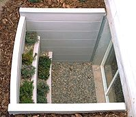 basement window well... great way to let in fresh air and light! and a cute plant/herb garden too.