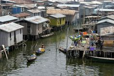Women sell food from their canoe. Poverty in the slum is fierce and the community is now s...