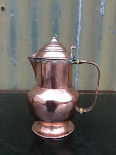 """SOLD. Lidded copper jug in the Arts & Crafts tradition. Hand-raised in bellied profile on soldered flared foot. The lid with concentric ring detail, pip terminal and thumb-piece above arcaded rim.  Flat, ribbed handle with bone collars.  The interior silver-lined.  No marks. Early 20th Century.  Very good order. Watertight. 6""""h.  B.G. 6137                                 £48"""