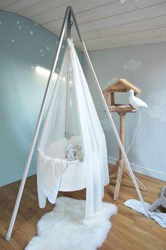 Chambre bébé cocooning : berceau au centre de la pièce, murs peints en bleu ciel, sol en parquet, esprit nature , voile vaporeux sur le berceau similaire à un nuage