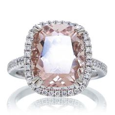 This feminine lovely pink cushion cut 12x10 mm morganite is surrounded by a gorgeous halo of sparkling diamonds. Flanked by a single shank solitaire that is simple, classic, and timeless. This beautiful ring can be worn with a matching diamond band as shown (sold separately as option). The morganite