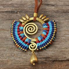 Shaped brass necklace with woven cotton details and brass drop