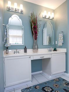 Neutral blue tones and decorative mirrors are feminine accents to this contemporary bathroom with a double vanity.