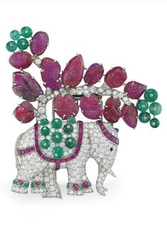 RENÉ BOIVIN - AN ART DECO RUBY, EMERALD AND DIAMOND ELEPHANT BROOCH, CIRCA 1939. Designed as an old-cut diamond elephant, with calibré-cut ruby and cabochon emerald headdress, onyx eye, calibré-cut ruby and emerald bead saddle and calibré-cut emerald and cabochon ruby anklets, to the old-cut diamond tree with carved ruby leaves and emerald bead fruit, 3 1/2 ins., with French assay marks for platinum, with maker's mark. #Boivin #ArtDeco #brooch Elephant Jewelry, Elephant Bracelet, Animal Jewelry, Elephant Gifts, Elephant Stuff, Jewelry Tree, Art Deco Jewelry, Antique Jewelry, Vintage Jewelry
