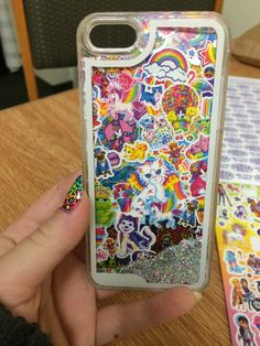 DIY Lisa Frank Iphone Case. I cut out a piece of paper the size of my phone and covered it in about two layers of Lisa Frank stickers. My phone case is the kind that are clear with the glitter in them so you can see whats on the paper that I place inside of it.