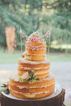 The naked cake, by Jefferey A. Miller Catering, echoed the rustic and whimsical reception with its chic undone look and festive bunting accents.