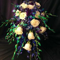 With purple/turquoise dendrobium orchids, ivory roses, blue delphinium, purple lisianthus and Deco Ice.