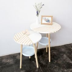 I'm thinking, one of those cheap side tables from the dollar store (the ones you cover with a table cloth) and a round wood tray from the thrift or craft store. There is a tutorial to make this table from wood and and paint buckets btw.