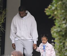 Daddy's girl: Kanye and North held hands as they later left the private event