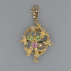 An Edwardian peridot, pink tourmaline and seed pearl pendant/brooch Of floral cartouche design, 5.0cm overall.