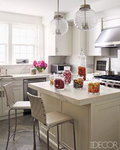 Furniture magnate Ashley Stark's Manhattan apartment kitchen features light fixtures from Chameleon Fine Lighting. The vent hood and cooktop are by Wolf and the dishwasher is by Bosch. See the full tour here.   - ELLEDecor.com