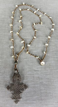 """Erb Jewelry - Paz has a 2-1/2-inch vintage silver Ethiopian cross on a crocheted strand of hammered fine silver beads with hand cut conch shell beads from Tibet. This 33"""" necklace is fastened with an abalone button clasp"""