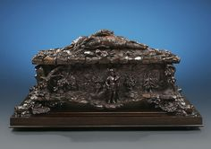 This Black Forest wine cooler is a celebration of the hunt, personified by the hunter and stag on the front panel. Standing in an elaborate forest setting, these figures are joined by the almost life-size carving of a rabbit, duck and smaller bird on the lid, and four boars' heads that serve as the cooler's feet. The rocky background, strewn with acorns, oak leaves and other foliage, provides the perfect stage for these highly detailed figures.