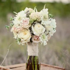 The bridesmaids will carry clutch bouquets of white anemones, blush spray roses, white peonies, white cymbidium orchids, and green sage wrapped in ivory ribbon with the stems showing.