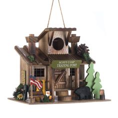 SCOUT CAMP TRADING POST BIRDHOUSE  (Item # 10016952)  Birds will love making this scout camp trading post their home! 'Its perfectly decorated with all the delightful trimmings you'd find during a summer camp getaway, including canoe paddles, American flag, and evergreen trees.   worthajoygifts.com