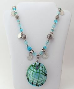 Trendy and fun. Necklace features an assortment of butterfly and sparkly beads that dress up a beautiful blue and green glass pendant.    Necklace: