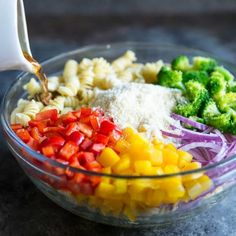 Easy Cold Pasta Salad Recipe - a photo of a clear bowl full various ingredients for a pasta salad on a dark blue background - click photo for full written recipe