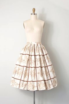 vintage 1950s full gathered skirt. finely detailed light brown rose sketch print on an ivory cotton background, thin brown trim creates grid pattern throughout, this band, hidden side metal zipper with one button closure. L A B E L Junior House Milwaukee       |      |     |     |     |   make sure to measure   |     |     |     |      M E A S U R E M E N T S waist 23 hips open length 26.75  will best fit an extra-small.  C O N D I T I O N excellent.