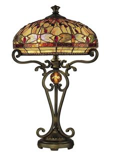 """$475 DRAGONFLY TABLE LAMP Muted shades of beige, golds, and ambers, with touches of red, provide a beautifully elegant Tiffany shade on this lovely lamp. The traditional dragonfly design is augmented by the almost-baroque metal base, which is finished in Antique Golden Sand . At 24"""", this lamp is large enough to handle the two 60-watt bulbs it takes, offering plenty of light. 16""""W x 24""""H"""