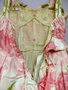 """Pierre Balmain Haute Couture pink crepe de chine floral party dress, 1957. At auction. Supported by several layers of acetate and tulle crinolines, the bodice fully structured with light boning and shaped with lingerie-style covered wiring and belting. Labeled """"Pierre Balmain / Paris / 88-627."""" Size 0/2."""""""
