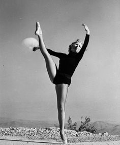 A dancer who is part of the promotion of nuclear testing at the Nevada Test Site, with a mushroom cloud in the background, April 6, 1953. U.S. Department of Energy photograph.