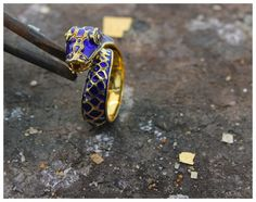 Blue enamel snake ring:  Vibrant and naughty.  This estate snake ring is crafted in 18K yellow gold and deep blue enamel.  Featuring scaled skin, hooded eyes, and a hissing mouth with a forked tongue.  Just what every woman wants.  Finger size is 7.25.