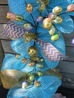 This garland is smothered in blue/turquoise deco mesh with ties of gold mesh ribbon, purple chevron burlap ribbon, rose gold ribbon and turquoise chevron ribbon. Throughout the center of the garland is an egg garland in blue, pink, green and purple with gold swirls. Chevron Burlap, Chevron Ribbon, Mesh Ribbon, Burlap Ribbon, Rose Gold Ribbon, Gold Ribbons, Green And Purple, Blue Gold, Deco Mesh Garland