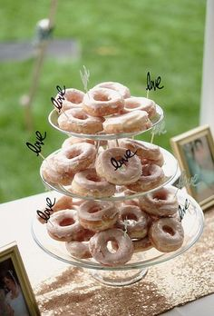 """A frosted donut tower decorated with gold pearls and """"Love"""" signs 