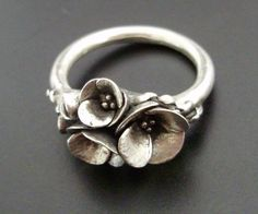 How pretty! I love this! With a diamond or two in center of flower(s) this would be a beautiful engagement ring, also