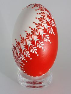 This is a goose egg pysanka. It is painted red and decorated with white and red wax. To create this egg, I use the pinhead method also known as the drop-and-pull pinhead method. In this method, mostly used in Poland, the Czech Republic, Slovenia, and Lithuania, a pin stylus is used as a tool. The head of the pin is dipped into hot wax and applied to the eggshell. There are two basic techniques used in this method - wax-embossed and wax-resist. This egg is wax-embossed, so the wax persists on…