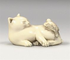An ivory netsuke 19th century Depicting a reclining cat, turning back to the left as it looks at a small bird, broken winged, on its back, a loose feather caught in the cat's fore paw, details delicately rendered, the birds eyes inlaid, signed Chokusai