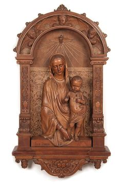 CARVED AND GILT DECORATED FIGURAL GROUPING OF THE MADONNA AND CHILD, ANTON JOSEPH REISS (1835-1900). At center, within an arched carved reserve, a three-quarters round carving of the Madonna and Child.