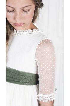 Vestido de muselina organdizada marfil con tul de puntos marfil, escote pico en espalda con botones forrados. Puntilla de encaje en cuello mangas y bajo. Lazo en tul verde., posibilidad de elegirlo en otros colores. Totalmente forrado.