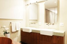 No banheiro do casal, os espelhos fixos ao trilho são, na verdade, portas de correr para nichos escondidos na parede. Pastilhas Vidrotil, madeira freijó (Mobília Brasil), metais Docol e louças Deca compõem o espaço projetado por Crisa Santos para o apartamento Itapaiuna