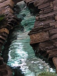 Water is supplied to five channels located at various heights in the sculpture. A dry stacked Owen Sound Limestone wall is intersected by the glass sculpture which offers a flow of water Mosaic Art, Mosaic Glass, Fused Glass, Stained Glass, Glass Art, Water Sculpture, Sculpture Art, Clay Sculptures, Glass Waterfall