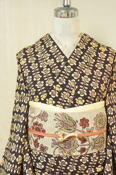 こっくりと深いチャコールブラウンの地に、北欧モダンファブリックのようにモダンにデザインされた椿模様が染め出されたウールの単着物です。