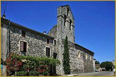 Photo au coeur de l'été du clocher-mur à 3 ouvertures de l?église Saint André construite de 1598 à 1699 contre l'enceinte fortifiée du XVe siècle, à Alba-la-Romaine, dans le département de l'Ardèche en région Auvergne-Rhône-Alpes.